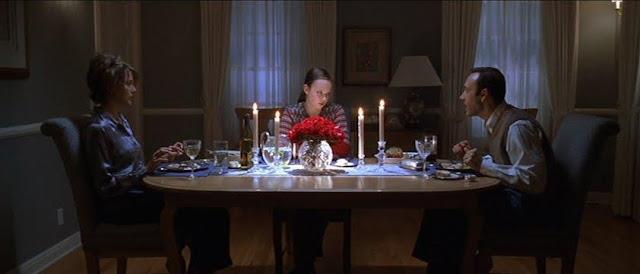La familia Burnham cenando, con Annette Bening a la izquierda, Thora Birch iluminada en el centro y Kevin Spacey a la derecha