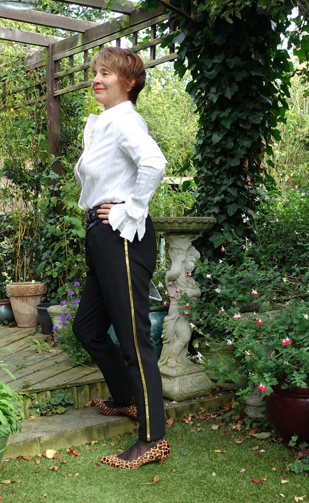 Image showing woman over 40 in black trousers with a gold side stripe and a frilled sleeve white tailored shirt