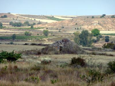 ondulado paisaje castellano reseco con motas de verde y cabaña pastoril de piedra en primer término