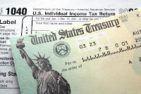 1040 tax form and refund check with the Statue of Liberty
