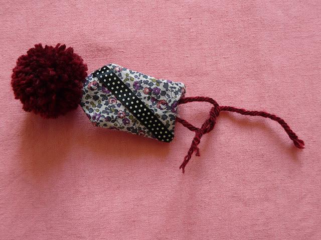 Nouer les brins de laine pour fixer le pompon