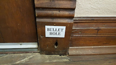 Photo of a bullet hole located at the Pecos Saloon.