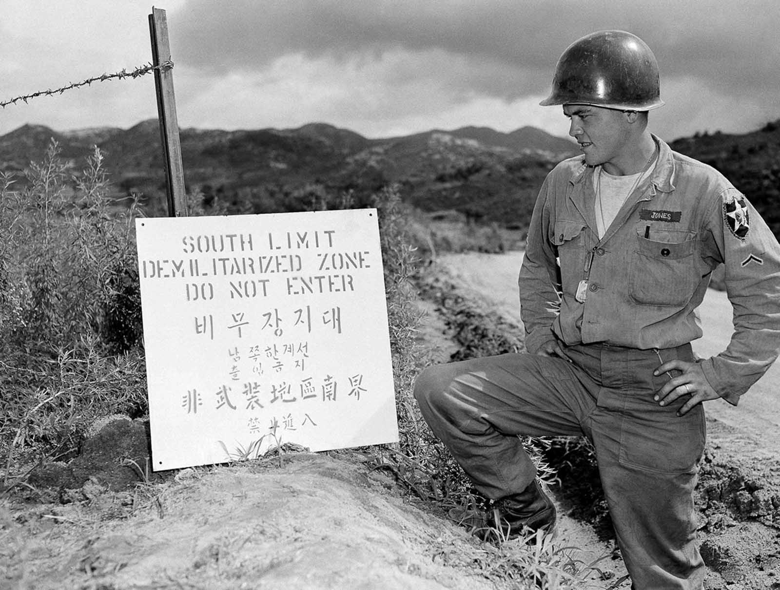 PFC Donald Jones of Topeka, Kansas, pauses to read a sign just posted on the south limit of the demilitarized zone in Korea on July 30, 1953.