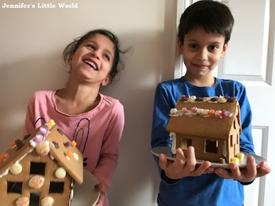 Children holding their finished gingerbread houses