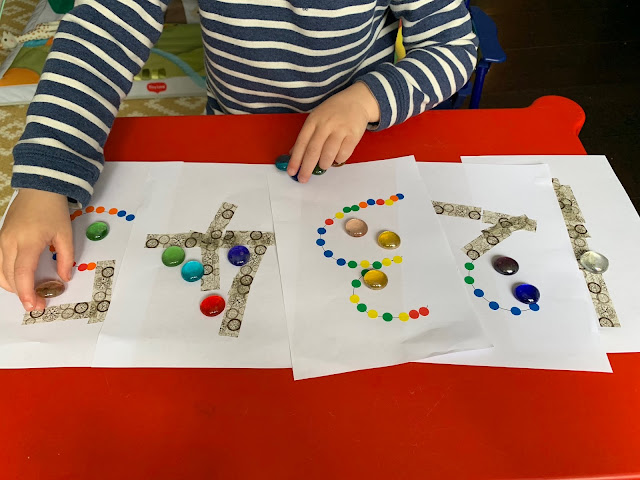 The numbers 1 to 5 with a toddler putting the correct number of counters on each one
