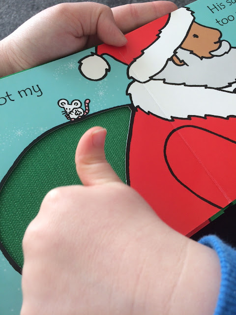 A children's book with fabric insert on the page, with a childs hand playing with it