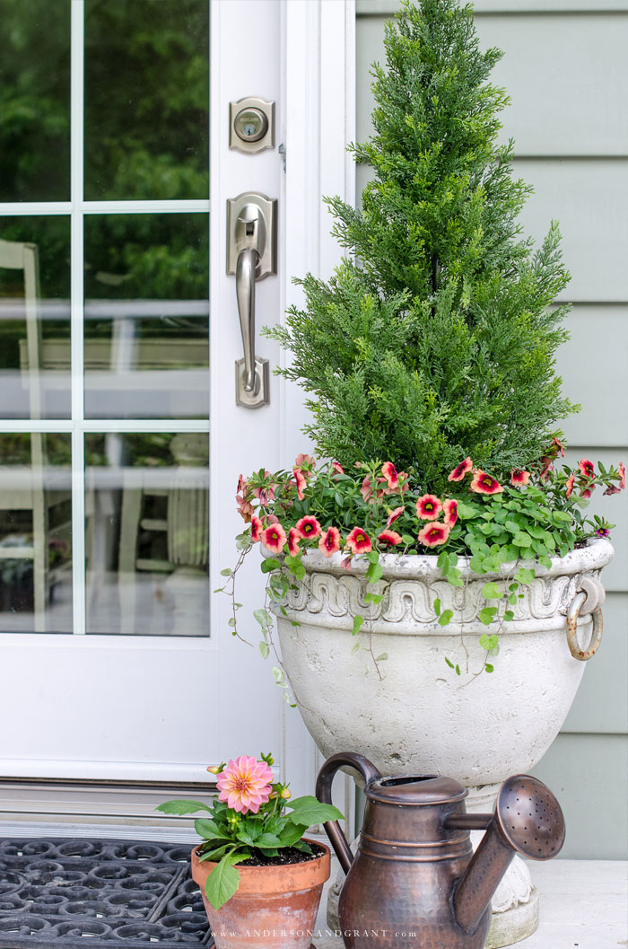 Dress up your front porch with faux shrubs and bushes in planters #porch #summer #gardening #andersonandgrant
