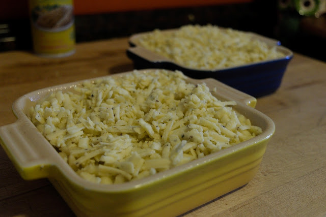 The mac and cheese in the baking dishes, topped with more truffled cheddar cheese.