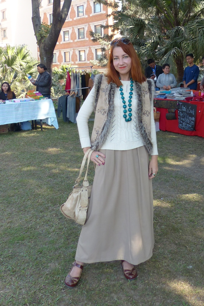 Embroidered fur trimmed vest over cotton sweater and maxi skirt