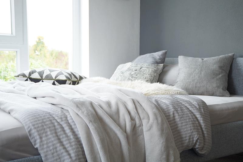 Schlafzimmer im Herbst einrichten und dekorieren in Grautönen und Weiß, mit vielen Wohntextilien für eine gemütliche Atmosphäre, Deko mit Fellen, Kissen, Decken, graues Bett mit Kopfteil, weiße und dunkelgraue Wandfarben und große Fenster