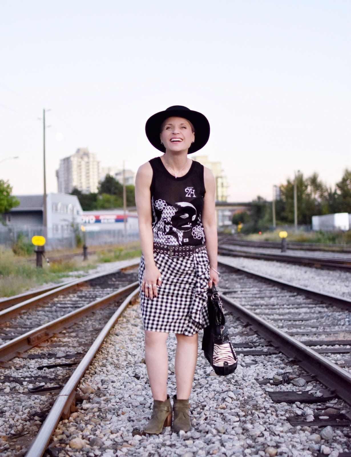 Monika Faulkner outfit inspiration - black and white graphic tank top and gingham skirt, olive suede booties, black felt fedora