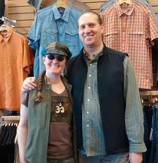 Woman and man standing next to each other, wearing vests over their clothing. The woman has a green vest on over a brown shirt and is wearing a green and brown 'newsboy' styled hat. The man has a black vest on over a green shirt