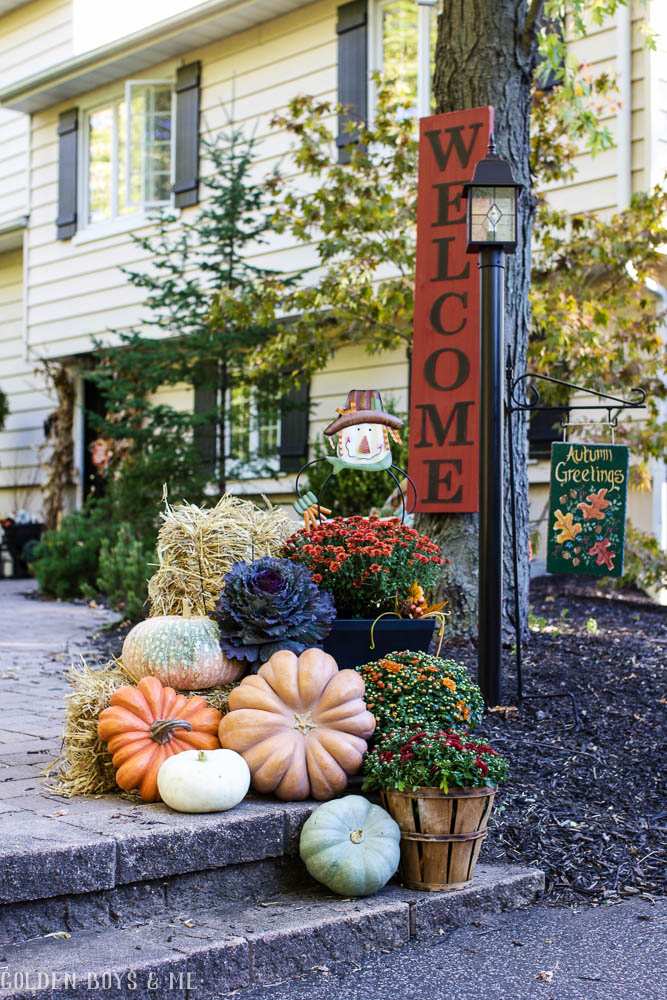 Front yard fall decor with large welcome sign, heirloom pumpkins, mums and hay bales