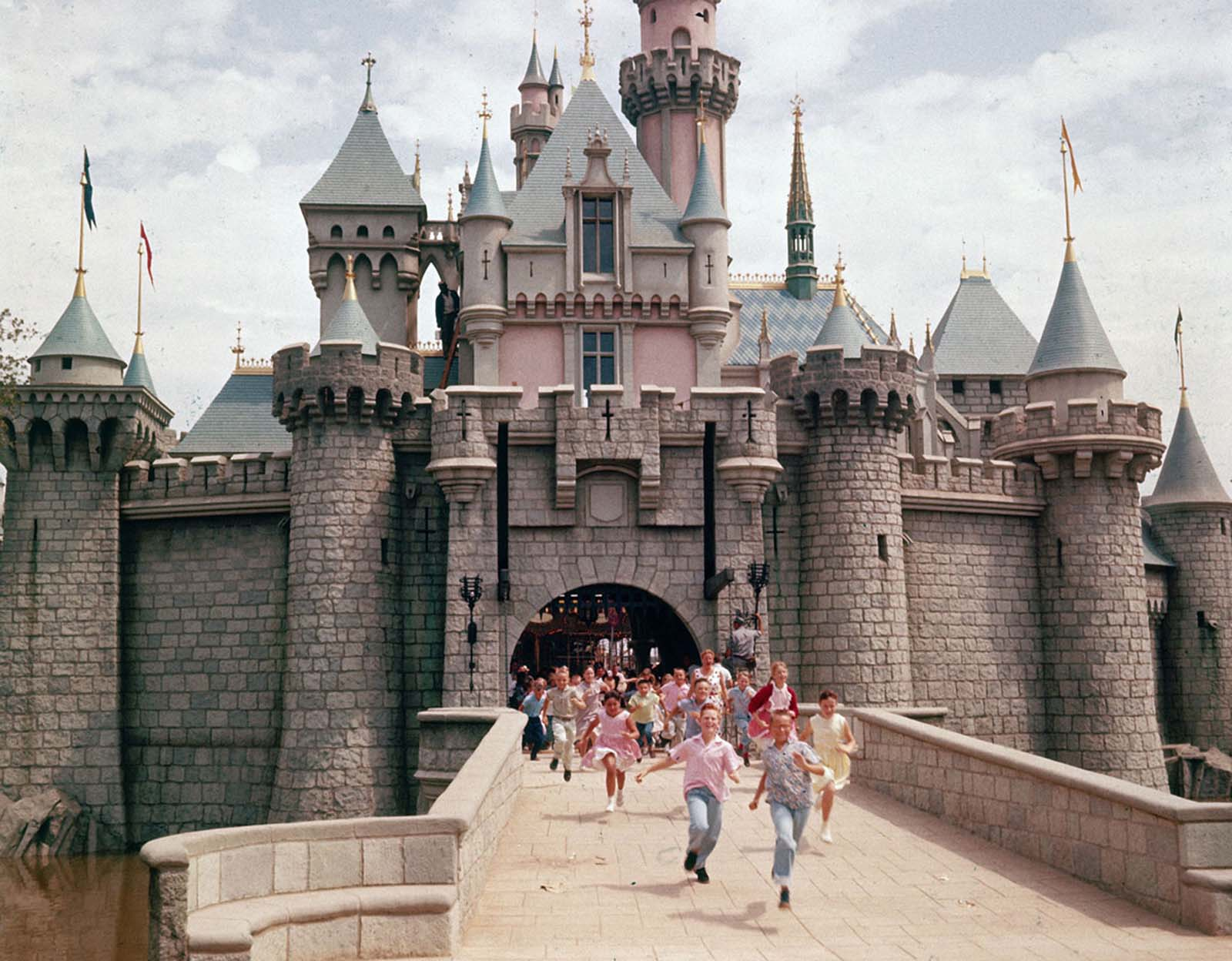 Children run through the gate of Sleeping Beauty's Castle at Disneyland, Walt Disney's theme park, in July 1955. The park opened to the public the week of July 17, 1955.