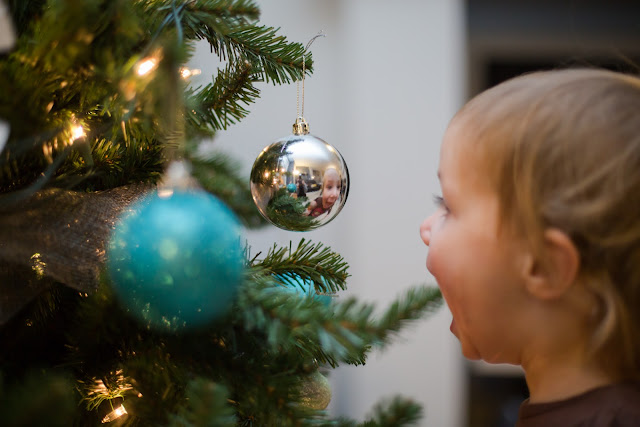 Child looking at reflection in ornament