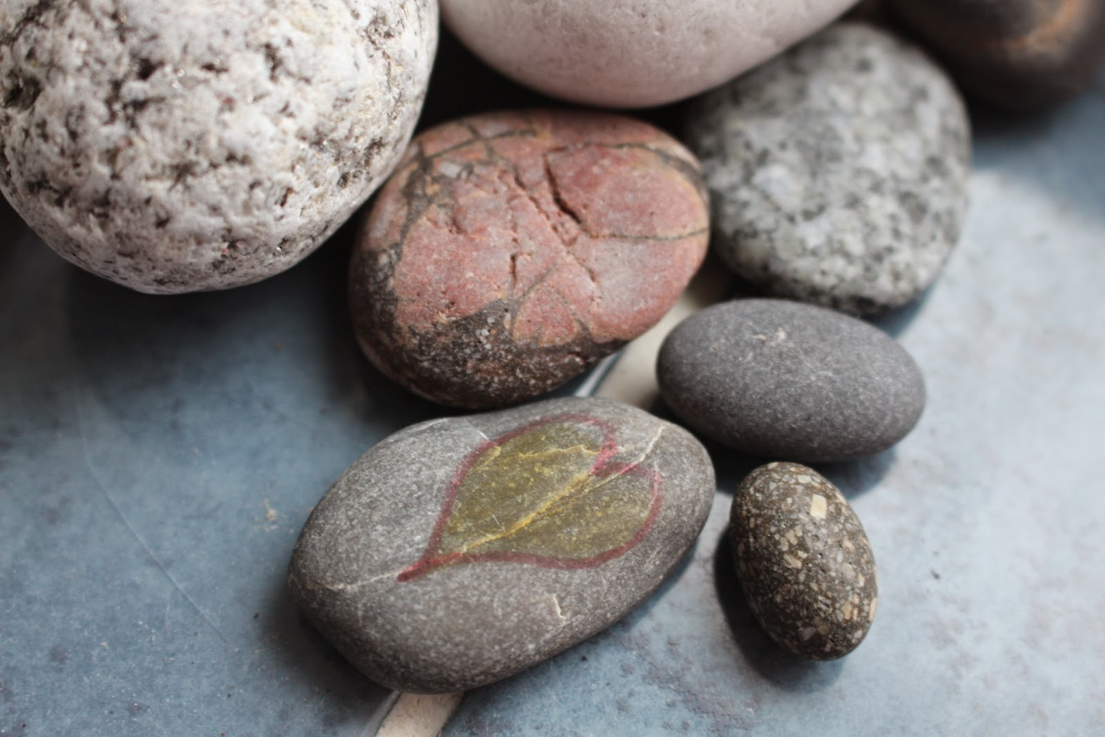 Some stones found on a beach with one having a heart design inked on it