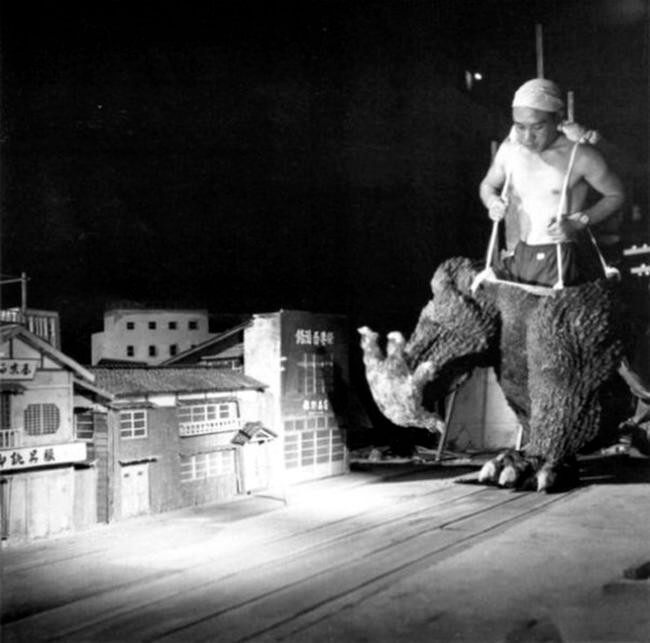 60 Iconic Behind-The-Scenes Pictures Of Actors That Underline The Difference Between Movies And Reality - The lower half of Godzilla terrorizes a poor Japanese town.