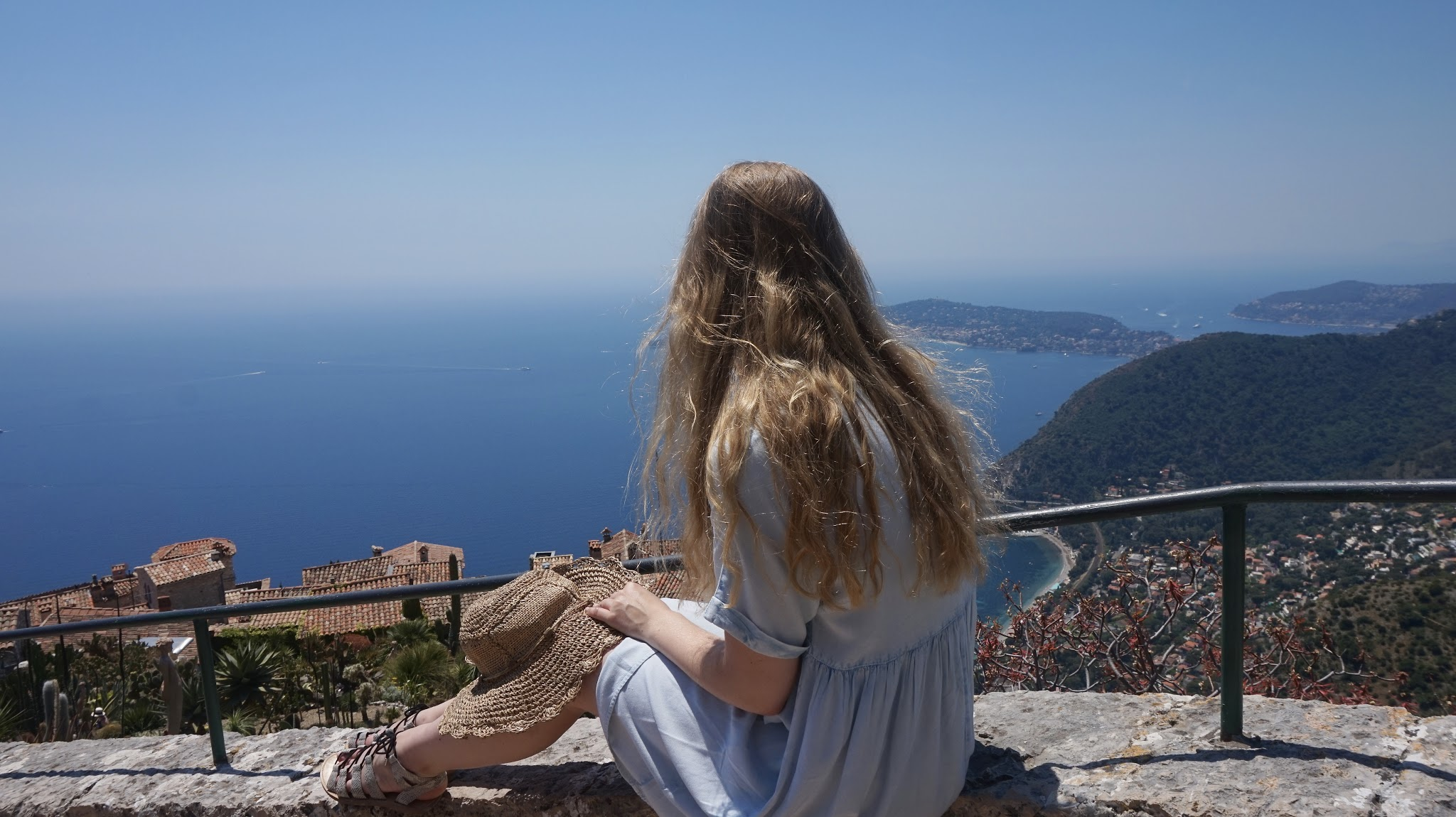 woman sits on a stone ledge overlooking the red rooftops, botanic plants and the sea