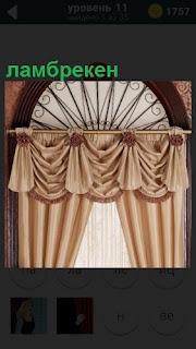 На окно подвешен карниз и к нему прикреплены ламбрекены