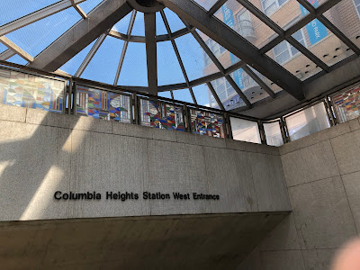 Photo of the glass roof, stained glass decorations, and concrete walls of the Columbia Heights Station West Entrance