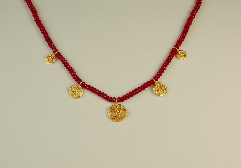 small red beads with yellow gold discs hanging