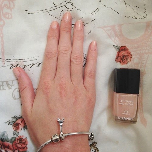 A nude chanel nail polish and nails painted in the shade