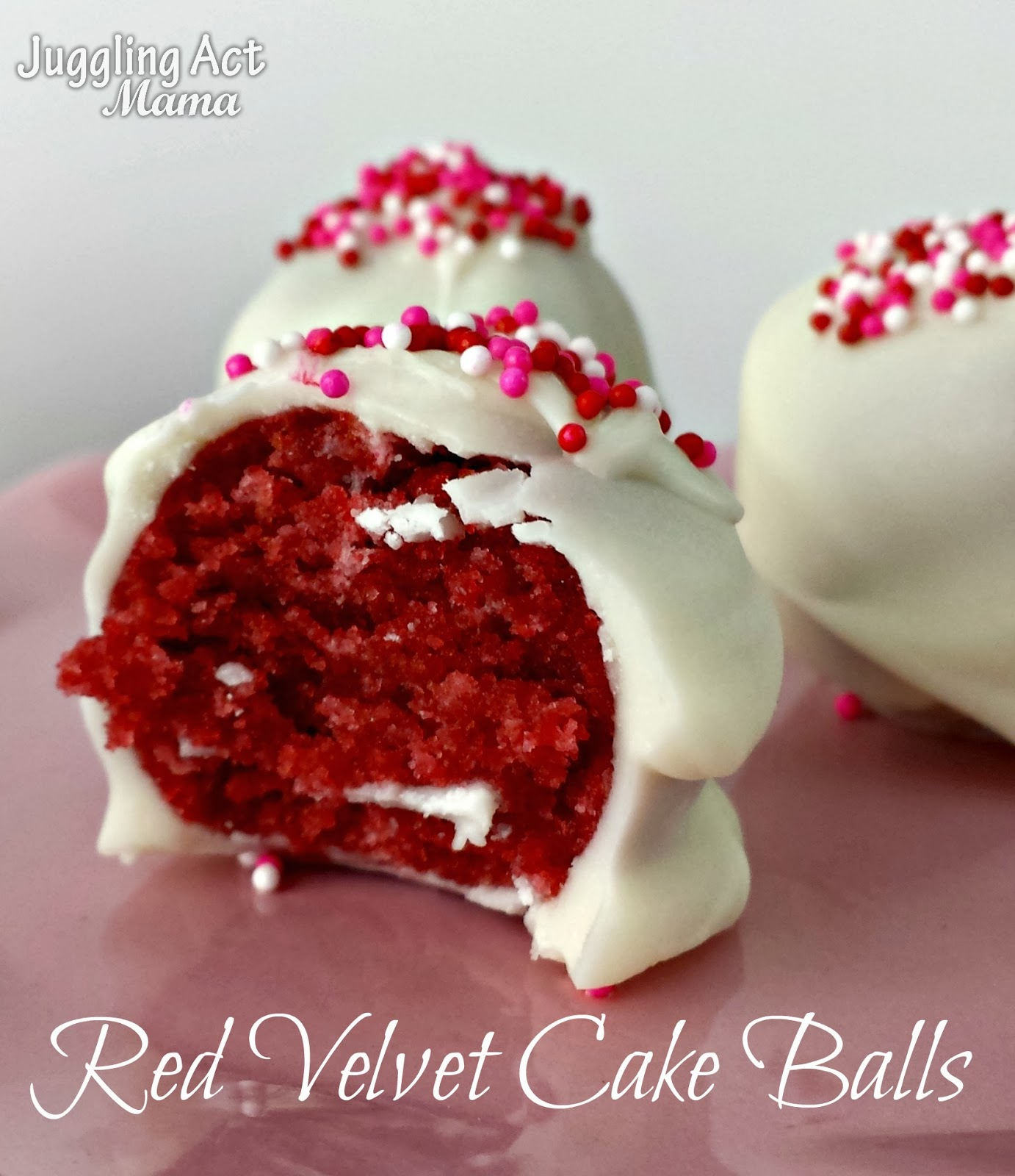 A Red Velvet Cake Ball Covered With White Chocolate Sits On Pink Plate