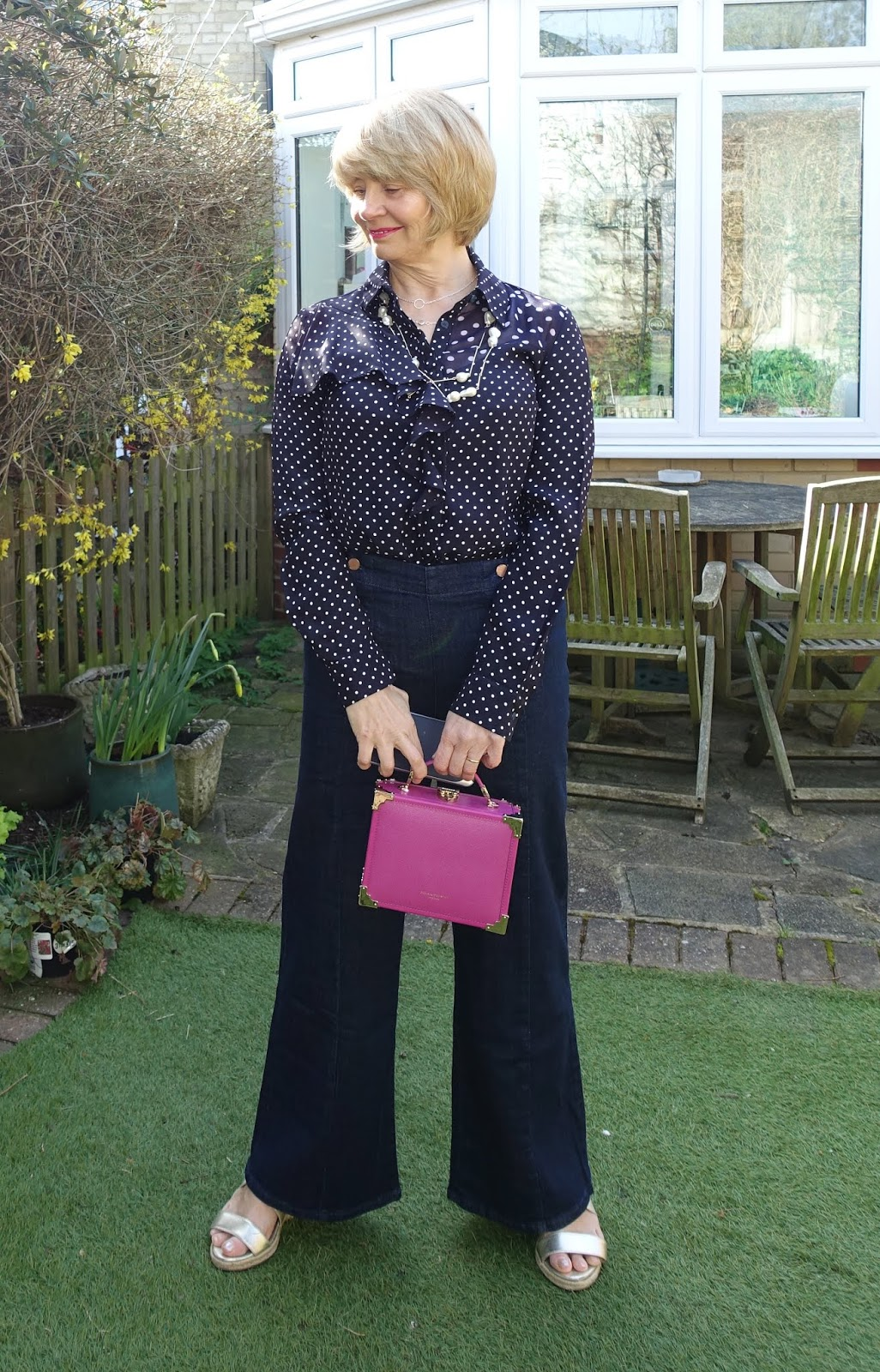 Dark indigo jeans in a flared cut from Boden worn with a polka dot blouse