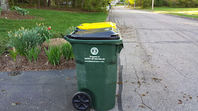 trash and recycling containers at curbside on a warmer day
