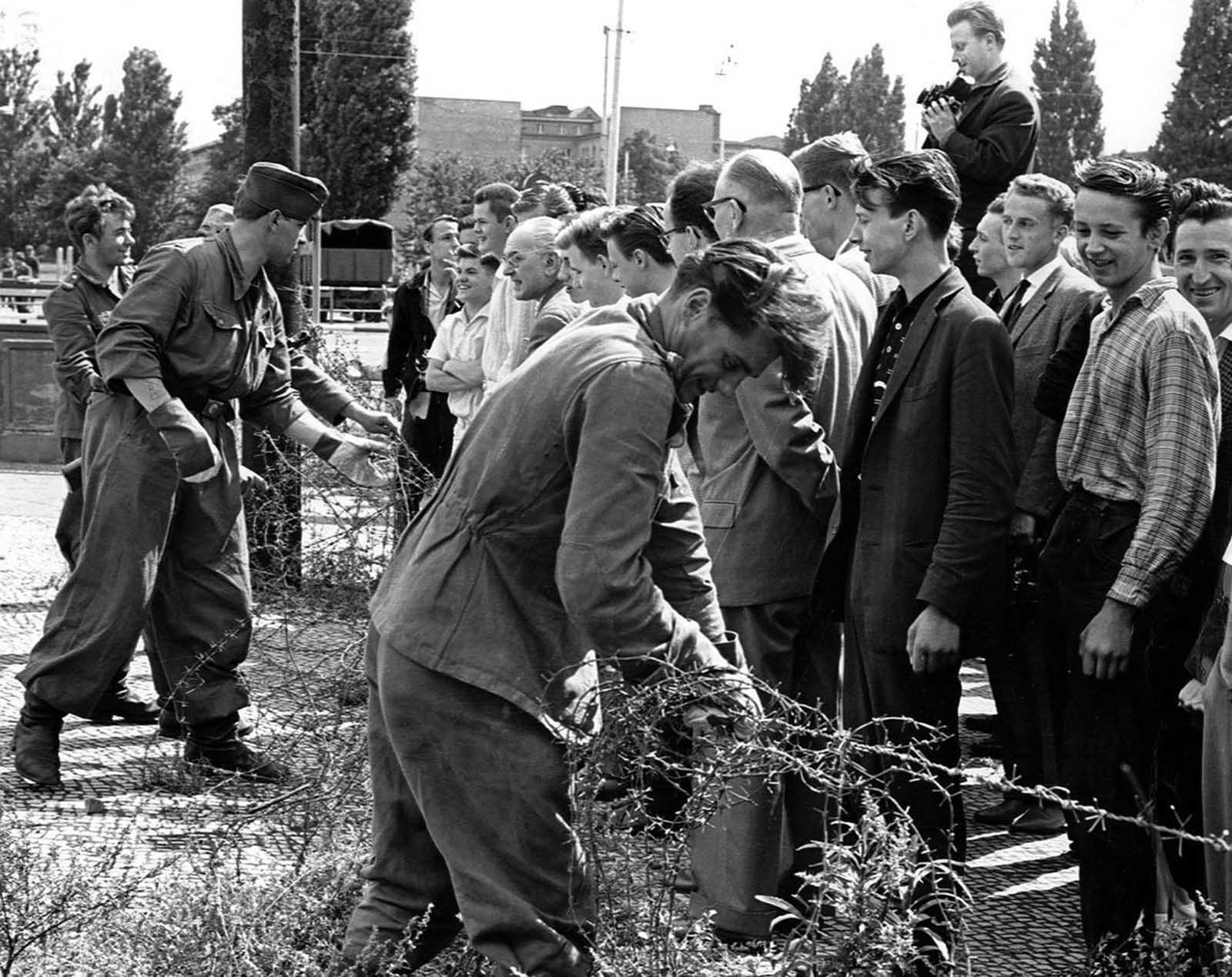 On August 13, 1961, East Germany closed its borders with the west. Here, East German soldiers set up barbed wire barricades at the border separating East and West Berlin. West Berlin citizens watch the work.