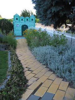 Path made from painted yellow bricks, leading to a miniature castle decoration.