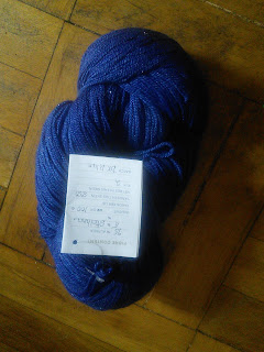 A skein of lace-weight yarn in a deep blue colour.