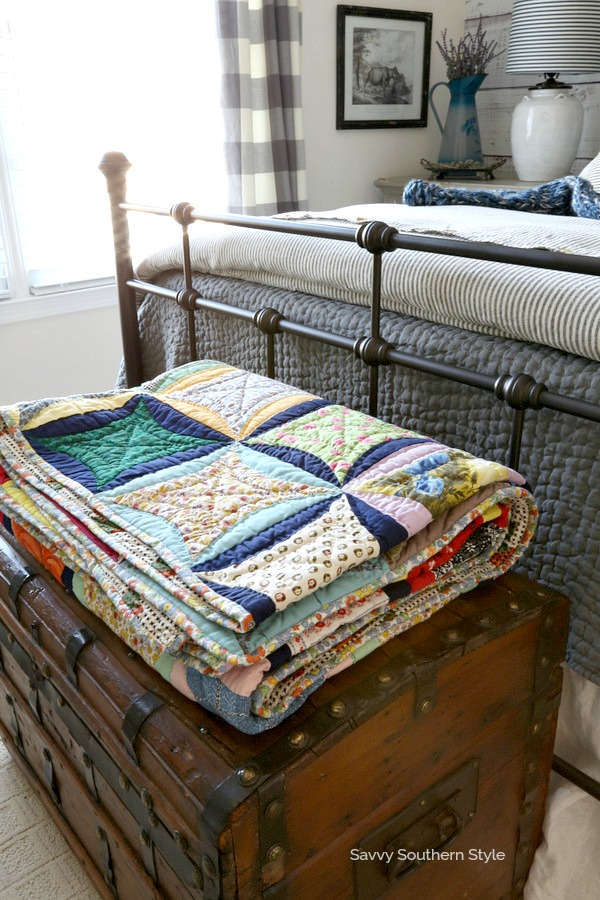 quilt on top of trunk in farmhouse style bedroom