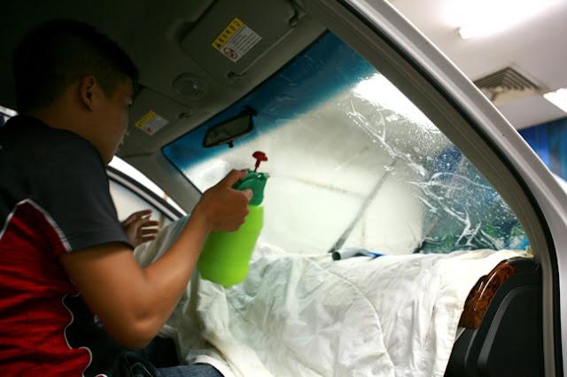 Kĩ thuật viên tiếp tục phun một lớp nước lên trên mặt phim vừa dán để giữ độ ẩm và giúp việc dán miết phim dễ dàng hơn.