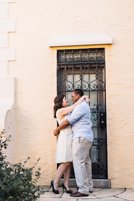 engaged couple in front of gated entrance