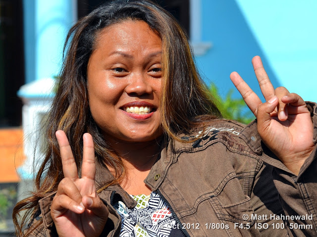 street portrait, Indonesia, Central Sulawesi, double V sign, modern Indonesian woman, charming, outgoing, smiling, posing