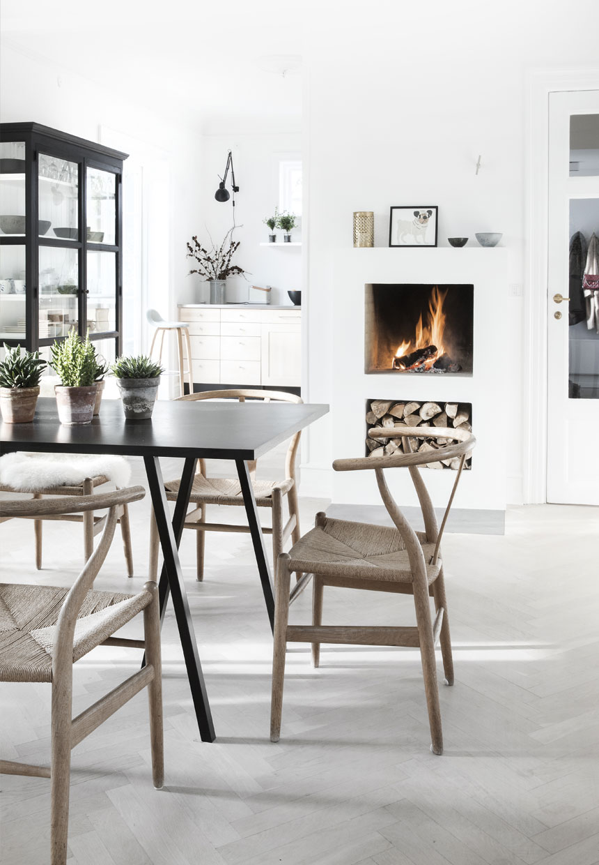 Wishbone chairs around black IKEA table, fireplace and serene scandinavian interior