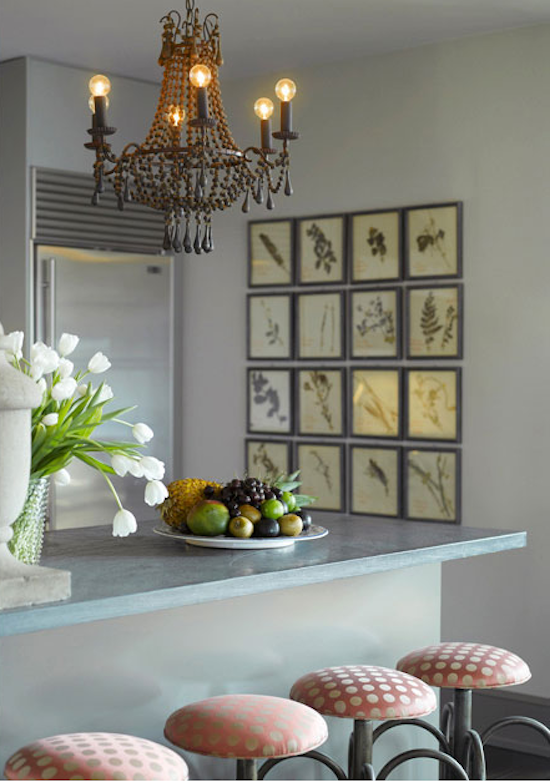 pressed flower art on a grid, round bulbs in a vintage chandelier, kitchen stools