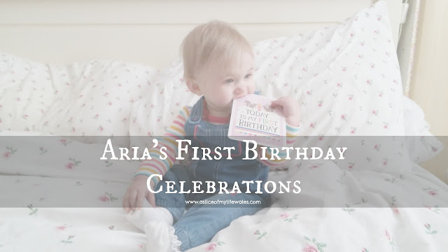 blog post about first birthday celebrations - baby sat on bed with first birthday milestone card