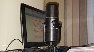 Un micrófono de sobremesa de color negro en primer plano y detrás una pantalla de ordenador en la web de Ver Sin Limites Accesibilidad