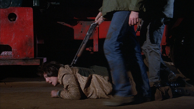 A man holds another man down on the ground with a shotgun