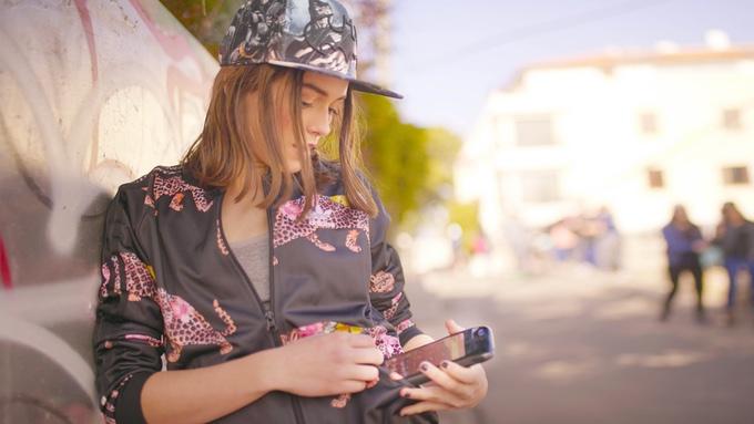 Eine stilsichere junge Frau hält ein iPhone in der Eye Android Hülle in der Hand