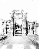 A black and white photograph of a highly ornamented stone archway.