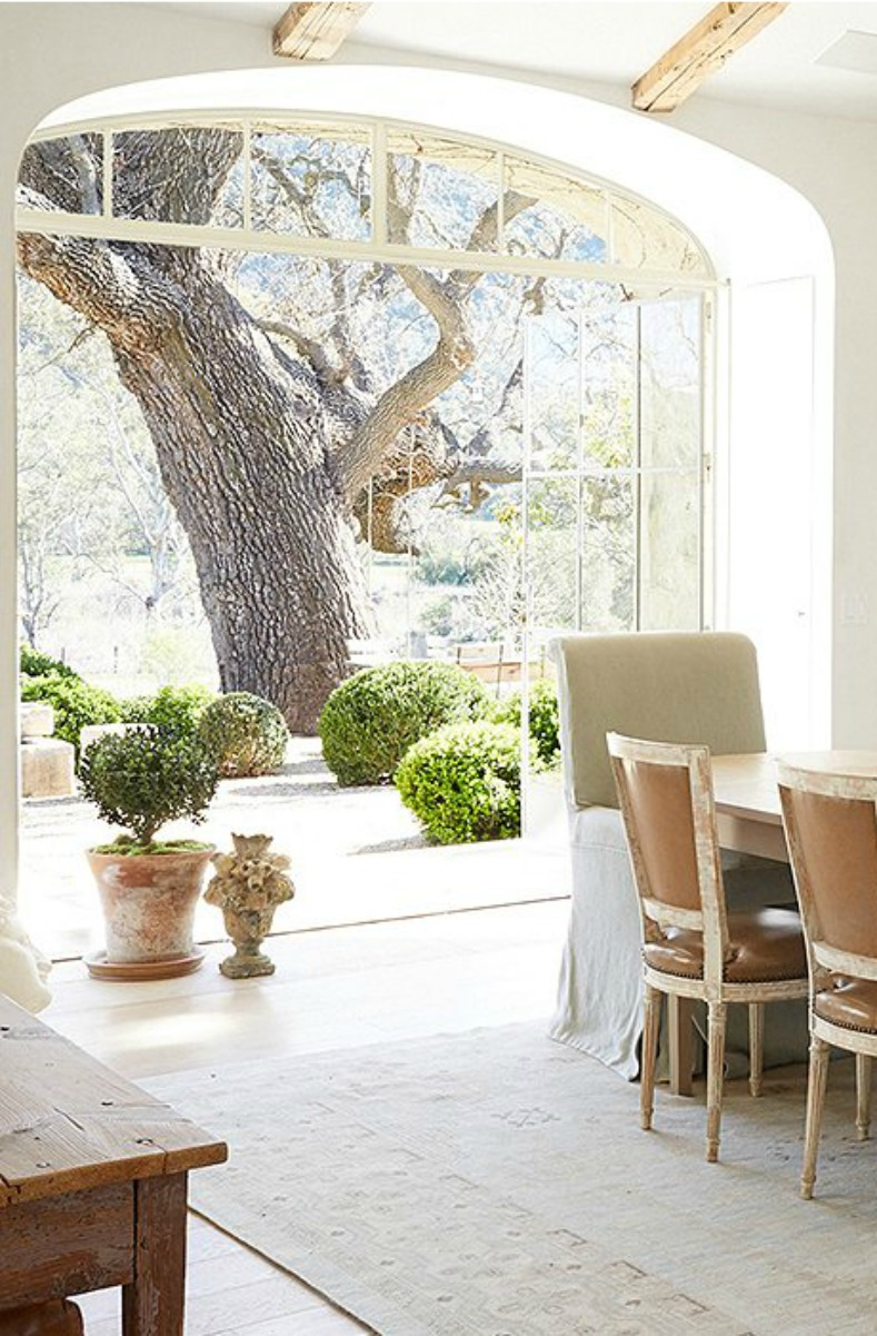 Patina Farm dining room with steel windows and doors and magnificent tree #modernfarmhouse