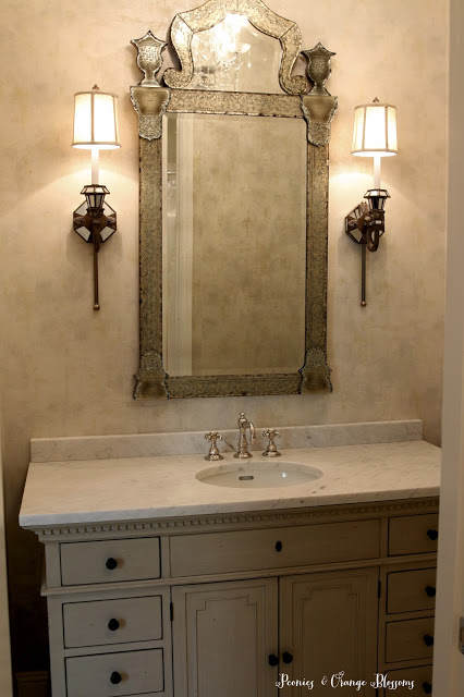 elegant bathroom with mirrored sconces, venetian mirror, and restrain hardware vanity!