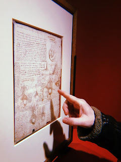 a hand pointing at a da vinci sketch