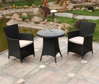 Mesa y sillas de mimbre en jardín zen