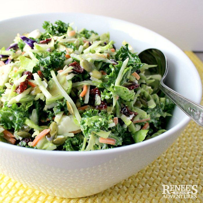 Close up of Broccoli, Kale, & Brussels Sprouts Slaw in white serving bowl with spoon