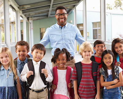 image of a teacher and students smiling at camera.