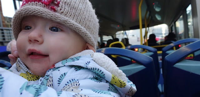 A baby in a warm hedgehog coat and woolly robin hat on the top deck of an open top bus